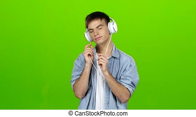 Guy listens to the music in the headphones and adjusts to...