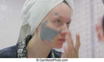 Woman doing cosmetic mask on her face