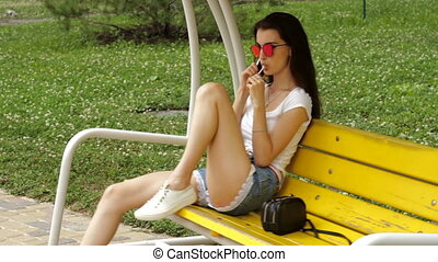 sexy girl sitting on a swing and sucks lollipop