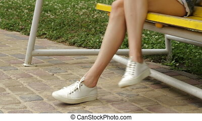 girl in white sneakers is sitting on a swing