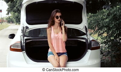 charming young girl talking on the phone and sits in the car