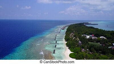 v03729 Aerial flying drone view of Maldives white sandy beach on sunny tropical paradise island with aqua blue sky sea water ocean 4k luxury 5 star resort hotel water bungalow hut relaxing holiday vacation