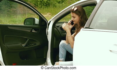 beautiful girl sitting in the car and talking on the phone -...