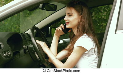 glamour lady sitting in the car while driving and talking on...