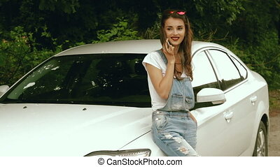 fashionable girl in denim overalls said by mobile phone near...