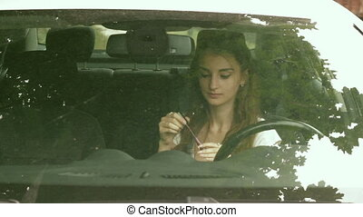beautiful girl sits in the car and paint lips - beautiful...