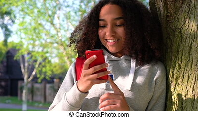 mixed race African American girl teenager leaning against a tree using a red cell phone