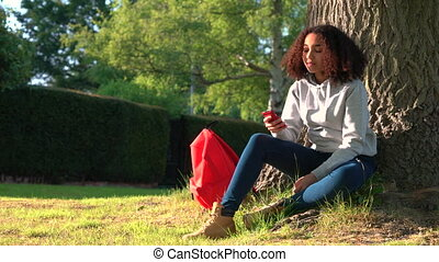 mixed race African American girl teenager sitting by a tree...