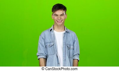 Guy cute smiles and shows two thrumbs up. Green screen - Man...