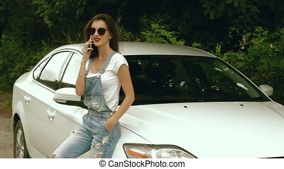 sexy girl with glasses says on a cell phone near car - young...