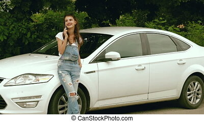 stylish brunette stands beside her car and talking on the...