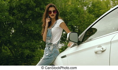 beautiful brunette with bright glasses stands near the car and tells op phone