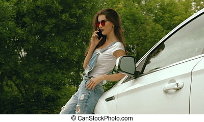 sexy girl in jeans dress stands near the machine and speaks...