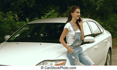 charming lady beside car says on a cell phone and smiling -...