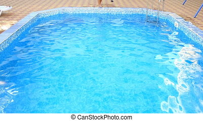 A man swims under the water in a pool with blue water. view...