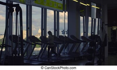 Unrecognizable girl walking on the treadmill in the fitness...