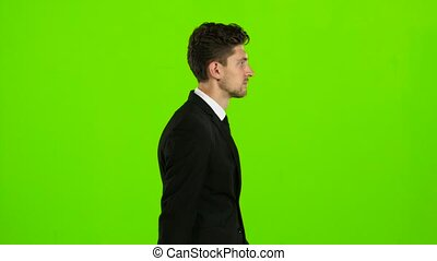 Man is going to a business meeting and waving greetings. Green screen. Side view