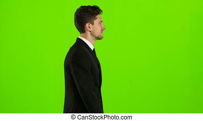 Guy walks calmly down the street, he is happy. Green screen...