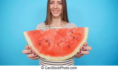 Pretty woman is holding a slices of watermelon a colorful...