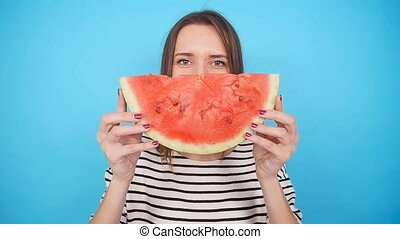 Pretty woman is holding a slices of watermelon