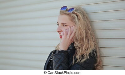 A beautiful young blonde in a leather jacket and wearing...