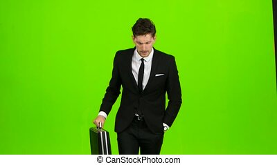 Businessman with a diplomat, a telephone rings to him and he starts running. Green screen