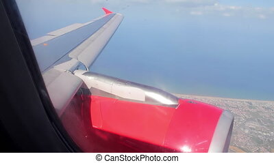 View through porthole airplane on sea and shore landscape and engine