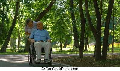 Senior woman pushing husband in wheelchair outside in summer...