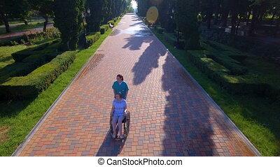 Aerial footage of nurse pushing elderly woman on wheelchair...