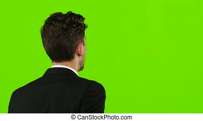 Man goes to work and talks on the phone. Green screen. Back view