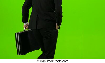 Businessman he has a diplomat in his hands, the phone rings and he starts to run. Green screen. Back view