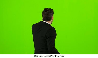 Man is a telephone rings to him and he talks. Green screen....