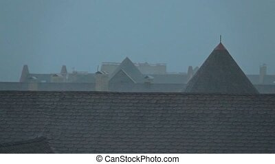 Sloping roofs of town houses in the rainfall. Slow motion...