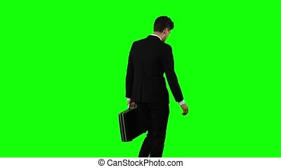 Businessman holds a briefcase in his hand, he rushes over it. Green screen