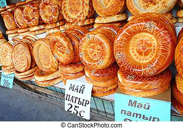 Flat cakes from tandoor on market counter in Bishkek,...