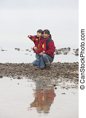 Mother and son on shoreline. - A mother and her little son...