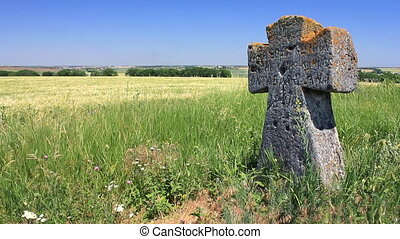 Ancient tomb cross in the green field Full HD