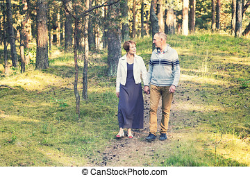 senior couple walking on forest trail holding hands