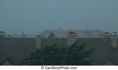 Sloping roofs of town houses in the rainstorm.