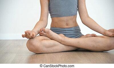 Little Girl Doing Namaste Sitting On Floor In Lotus Position