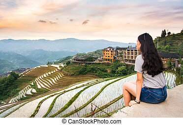 Girl enjoying sunset at terraced rice field in Longji, China...