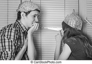 Teens boy and girl in hats made of aluminum foil, protect...