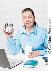 Girl with an alarm clock in a blue shirt in the office at...
