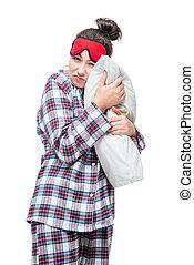 Sleepy woman in pajamas hugging her favorite pillow against...