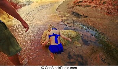 Girl Barefoot Plays in Shallow Fairy Stream by Rocks -...