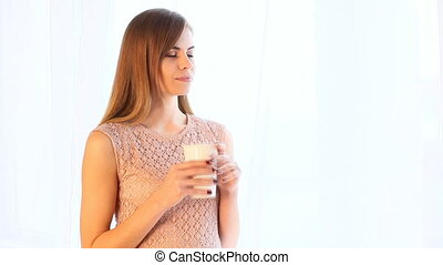 girl drink hot tea or coffee while standing at the window 1