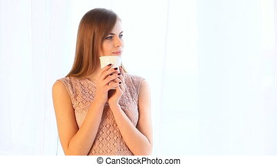 girl drink hot tea or coffee while standing at the window