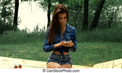 beautiful lady in shirt sits on the street and holding a phone