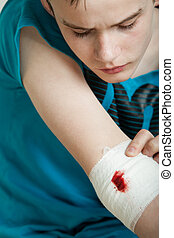 Teen boy looking at wounded and bandaged elbow