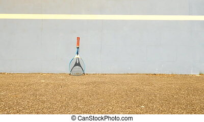 Very old aluminum tennis racket with old practice tennis wall, yellow ball playing on the court